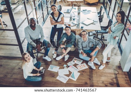 Multiracial young creative people in modern office. Group of young business people are working together with laptop, tablet, smart phone, notebook. Freelancers sitting on the floor with documents.