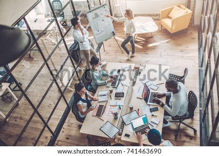 Multiracial young creative people in modern office. Group of young business people are working together with laptop, tablet, smart phone, notebook. Successful hipster team in coworking. Freelancers #741463690