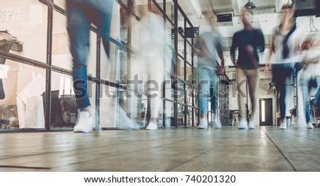 Multiracial young creative people in modern office. Successful hipster team in coworking. Businesspeople walking in the corridor of an business center. Motion blur.
