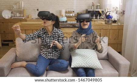 Multiracial young female people wear virtual reality glasses. asian best friends roommates having fun using new technology testing vr goggles connection with futuristic visions. girls laughing happy. #1467049805