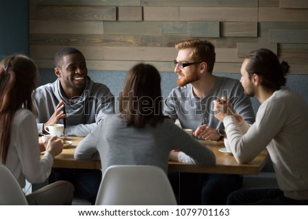 Multiracial young friends talking drinking coffee together sitting at cafe table, african man telling joke while diverse millennial smiling people enjoying listening having fun at coffeehouse meeting