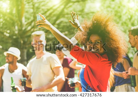 Multiracial young people dancing in forest party in summer time - Cheerful multi ethnic friends drinking outdoor - New music entertainment trends  - Focus on black girl - Vintage retro editing