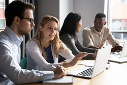 Multiracial younger and older colleagues working in pairs in office. Skilled female employee explaining focused male coworker new software. Confident manager discussing project details with client.