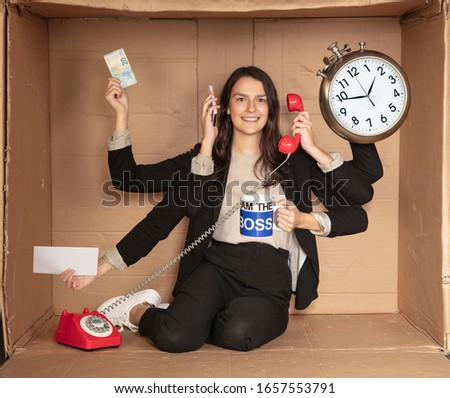 multitasking businesswoman sitting in a cardboard office, doing a lot of things at once Сток-фото ©