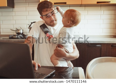 Multitasking Father Working From Home On Laptop With Baby daughter