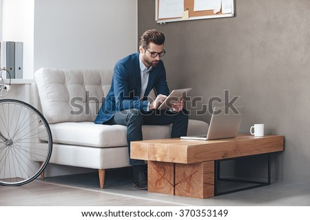 Multitasking. Handsome young man wearing glasses and working with touchpad while sitting on the couch in office