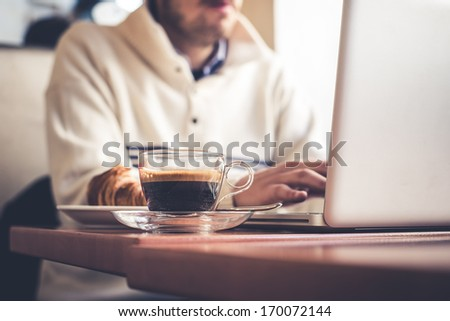 Multitasking Man Using Tablet, Laptop And Cellphone Connecting Wifi