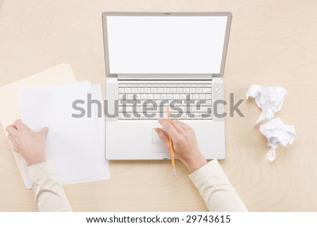 Multitasking  -  overhead shot of hands using computer and holding blank paper