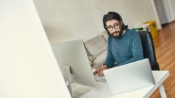 Multitasking. Young caucasian concentrated bearded man sitting at his workplace and working remotely, using desktop computer and laptop. Freelance, home office. Focus on man. Stay home, self isolation