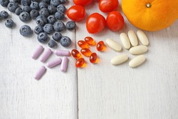 multivitamin supplements from fruit on white wooden background