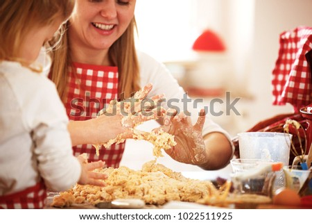Mum and daughter spending time together making dough.  #1022511925