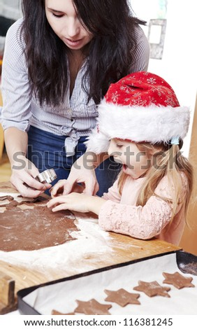 mum and her daughter cutting gingerbread cookies - stock photo