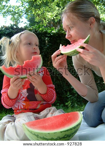 Mum and her daugther eating watermelon