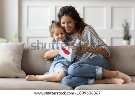 Mum and little daughter sit on sofa in cozy living room hold paper card read wishes on handmade postcard. Attentive small kid made gift on International Women Day to loving mom, Mother Day celebration