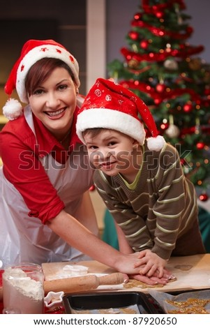 Mum and son having fun at christmas baking, looking at camera, smiling.?
