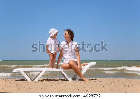 Mum and the child sit on chairs near the sea.