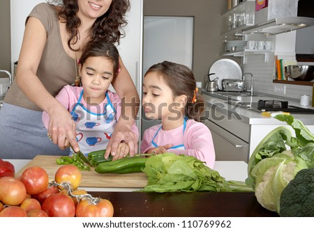 Mum and twin daughters learning to chop vegetables together in the kitchen, using a chopping board and surrounded by fruit and vegetables.