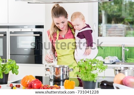 Mum cooking with baby in arm in her home kitchen #731041228