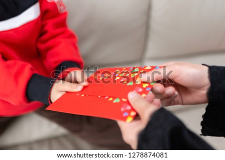 mum giving a red pocket to her son #1278874081
