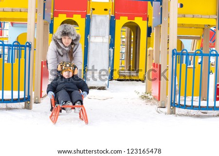 Mum giving her young son a toboggan ride in the snow front of the colourful equipment of a childrens playground
