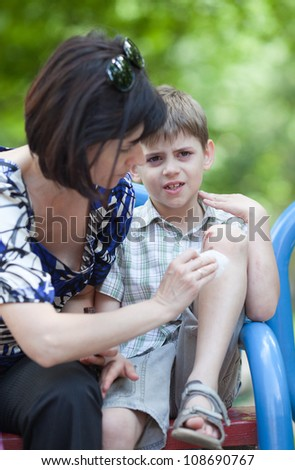 Mum helping her son who scraped his knee