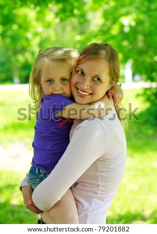 Mum holds the small daughter outdoors smiling