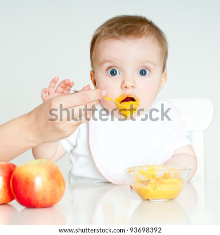 Shutterstock Mum spoon-feeds the child