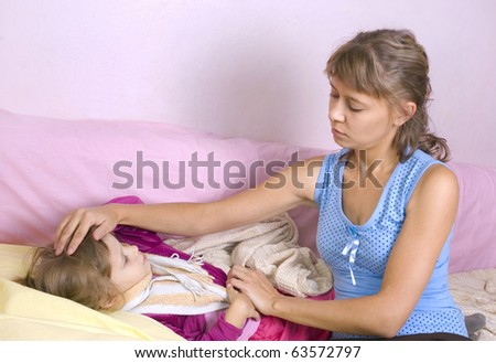 Mum touches a forehead at the sick child - stock photo