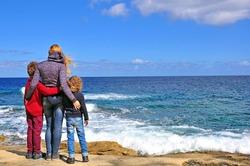 Mum with kids standing at the Mediterranean sea, Malta
