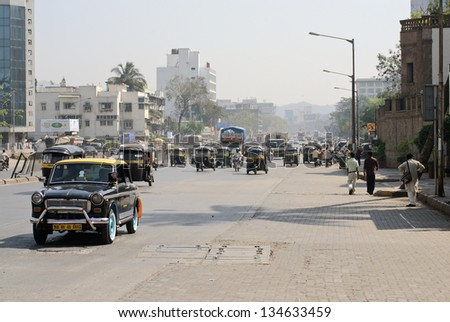MUMBAI, INDIA - JANUARY 27:  Traditional indian black and yellow taxi drive along Mathuradas Vasanji Road on January 27, 2008 in Mumbai