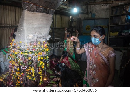 MUMBAI/INDIA - June 5, 2020: A women wearing mask tie threads and perform puja around Banyan tree on the occasion of Vat Purnima at Dharavi