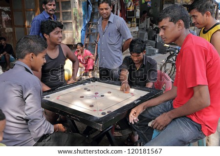 MUMBAI, INDIA -NOVEMBER 27:Men playing board game on street on Nov. 27, 2010 in Mumbai. Board games have been played in most cultures and societies throughout history.They are still  popular in India