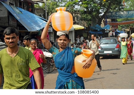 MUMBAI,INDIA-NOVEMBER 26:Woman carrying water on Nov.26, 2010 in Mumbai.In India women fetching water spend 150 million work days per year, equivalent to a national loss of income of 10 billion Rupees