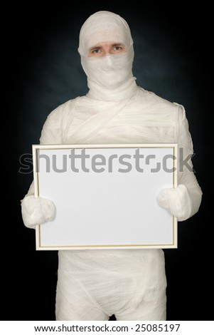Mummy with blank frame on the black background