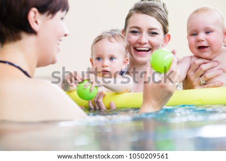 Mums being happy about their baby kids playing with each other in water #1050209561
