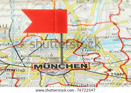 Munchen (Munich) - famous city in Germany. Red flag pin on an old map showing travel destination.