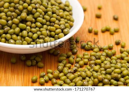 Mung beans in white bowl on wooden tabletop