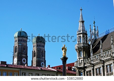 Munich. Detail of the town hall on Marienplatz withe statue of Virgin Mary. In the background, the mighty towers of church Frauenkirche.