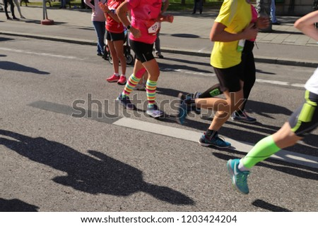 MUNICH, GER - OCTOBER 14, 2018: Running feet with sports shoes at the GENERALI MÜNCHEN MARATHON. Legs with short trousers, colorful socks and shoes in motion. Selective focus, intentional blurry. #1203424204