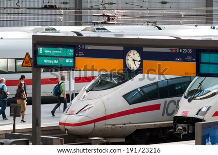 MUNICH, GERMANY -  MAY 25, 2010: Munich main central train station platform view, with a high speed ICE train, timetable, running travelers clock on platform at Hauptbahnhof on May 25, 2010 in Munich. #191723216