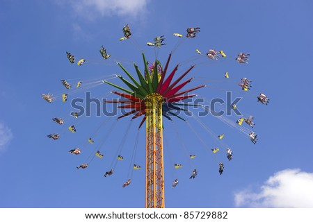 """MUNICH, GERMANY - SEPTEMBER 21: chairoplane with flying people of world biggest beer festival """"Oktoberfest in Munich"""" on September  21, 2011 in Munich, Germany"""