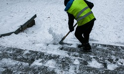 Municipal services are engaged in snow removal after a snowfall. A worker removes snow from the street with a shovel.