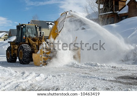 Municipal snow blower clears snow-covered streets producing a plume of snow