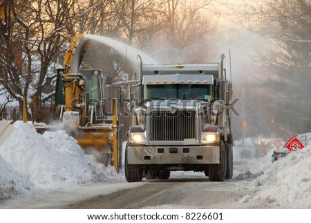 Municipal snow removal crew at work; snow thrower and dump truck on street of snow