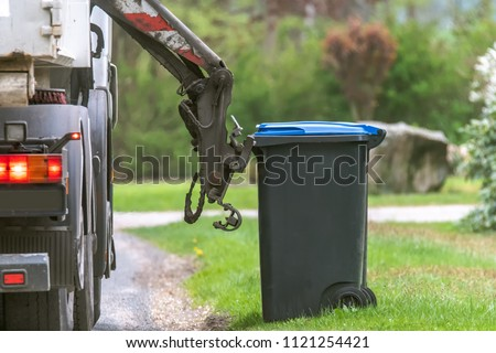 Municipal waste disposal. With a special car garbage truck, the garbage from the garbage bin is loaded into the car. Concept: Waste disposal and cleanliness
