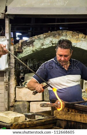 MURANO; ITALY - JUL 01: Traditional Glassmaker of Murano. Murano is the most famous place for handmade glass production with Murano glass by Artisan glassworker in Murano, Italy on July 01, 2011.