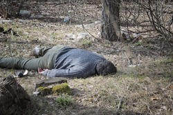 murder in the woods, a dead man in a blue sweater and green pants lying on the ground among the trees in the woods
