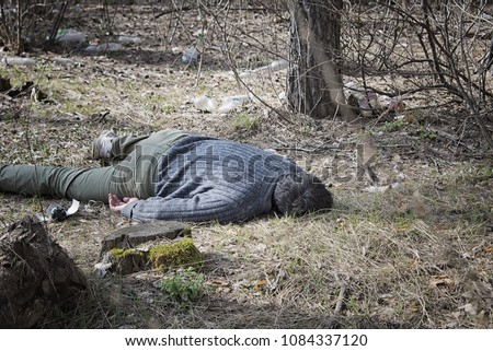murder in the woods, a dead man in a blue sweater and green pants lying on the ground among the trees in the woods Foto stock ©