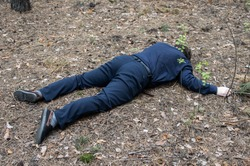 Murder in the woods. The body of a man in a blue shirt and trousers lies on the ground among the trees in the forest. Victim of an attack. Horizontal photo.