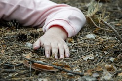 Murder in the woods.The hand of a dead teenager in the forest on the ground. Victim of violence. The concept of child abuse. Close up.